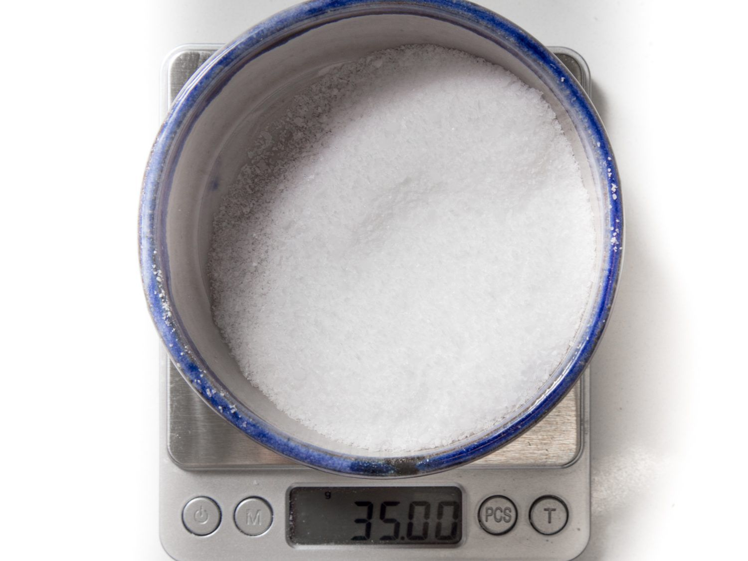 Overhead view of a bowl of salt sitting on a scale.