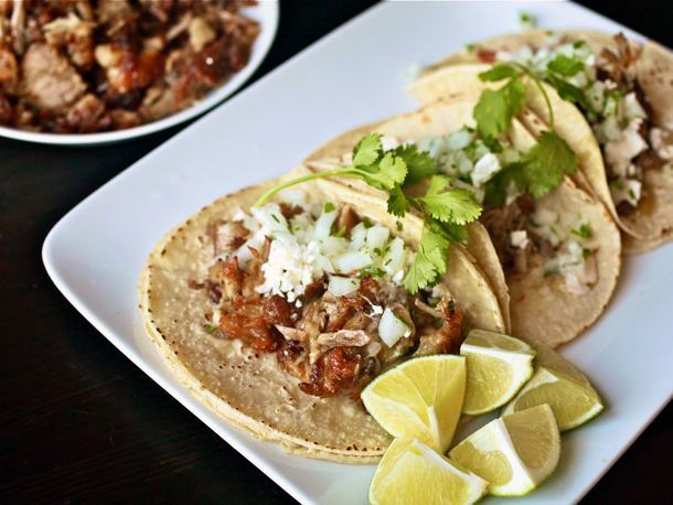 Three carnitas tacos topped with onion and cilantro on a white plate with lime wedges on the side.