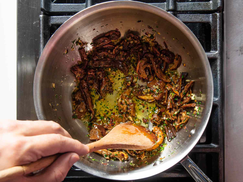 Sautéing rehydrated porcini mushroom slices in olive oil for spaghetti alla carrettiera