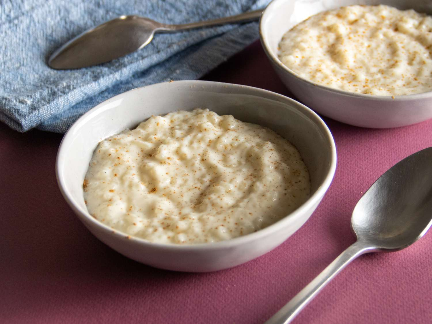 a side close up of rice pudding with cinnamon in two bowls
