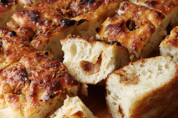 Easy no-knead garlic focaccia cut into squares, with one flipped on its side to reveal a clove of roasted garlic.