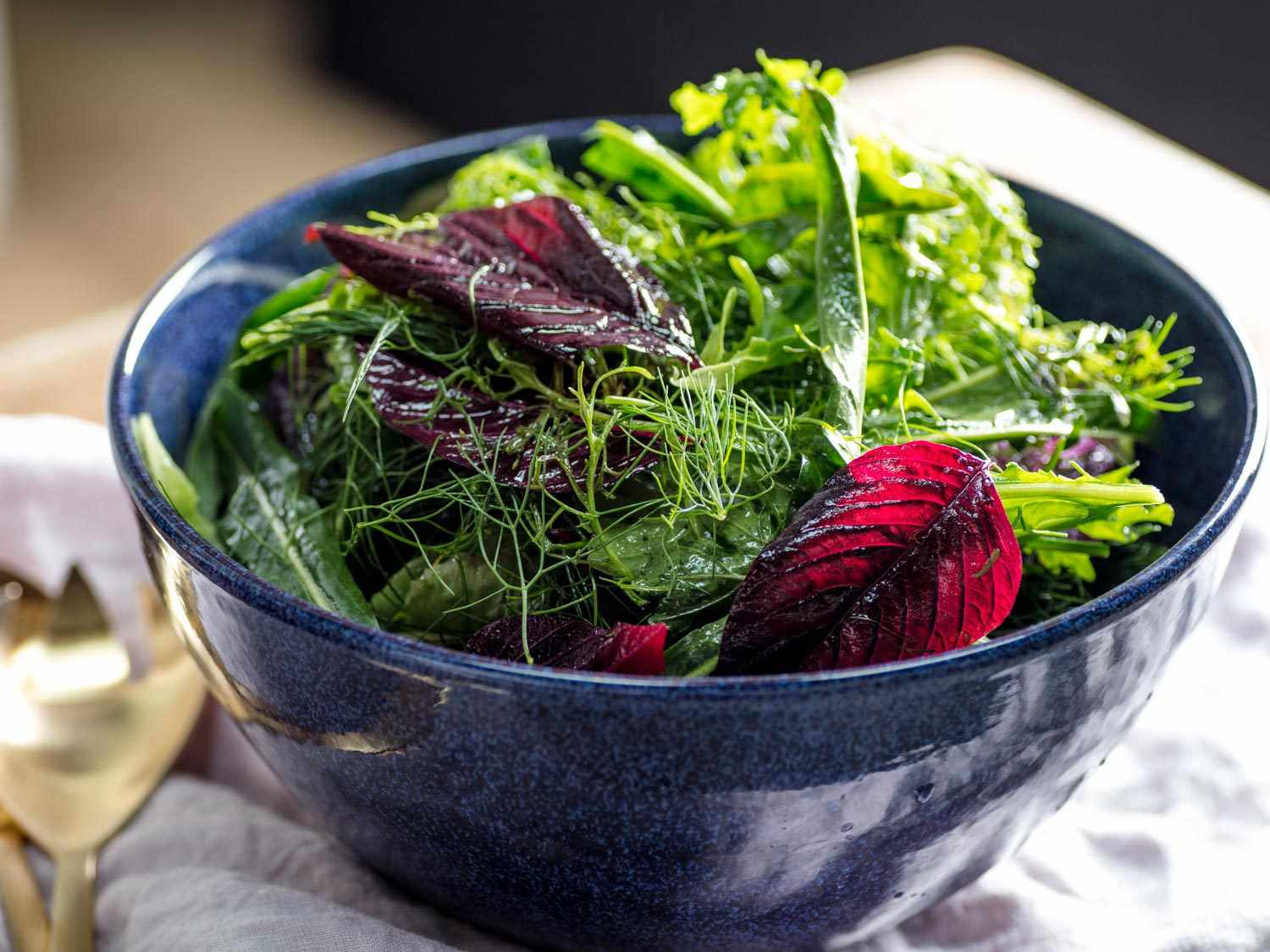 Dressed mixed greens salad in a blue bowl