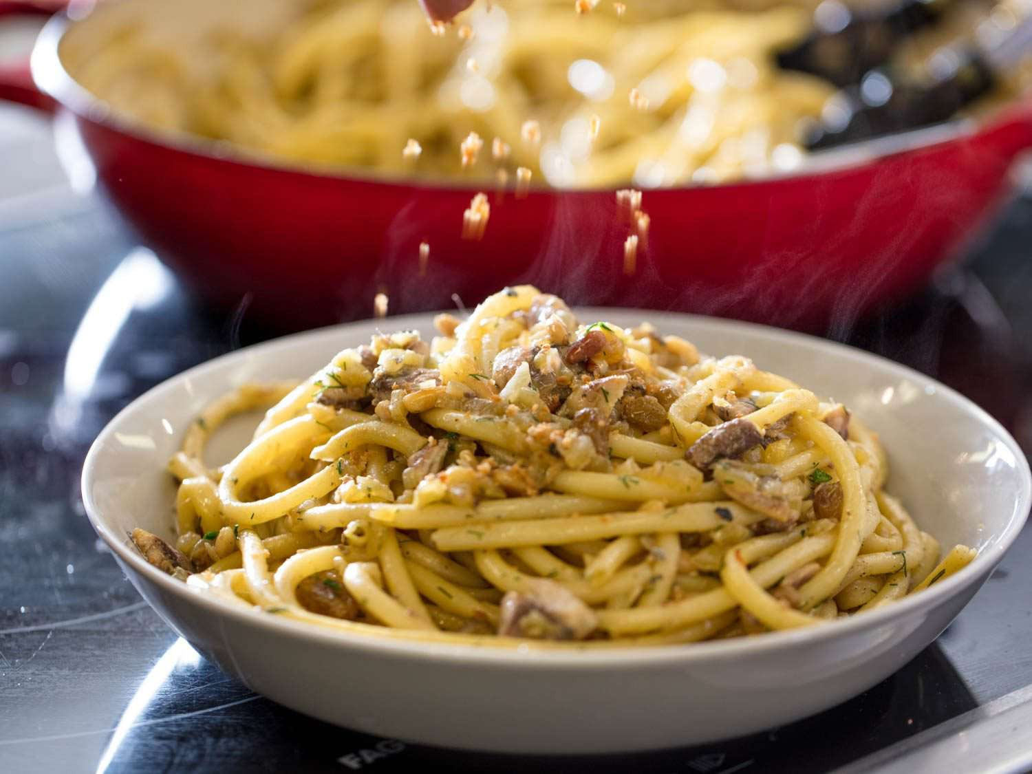 Sprinkling additional breadcrumbs over a finished dish of Sicilian pasta with sardines.