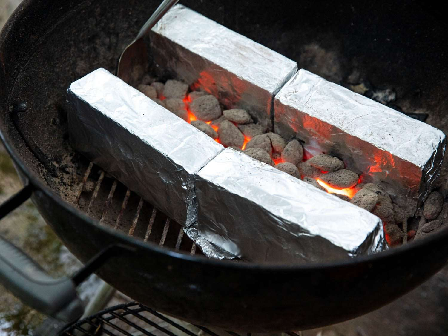 Arranging glowing coals between two parallel walls of foil-wrapped bricks for cooking skewers in a kettle grill.