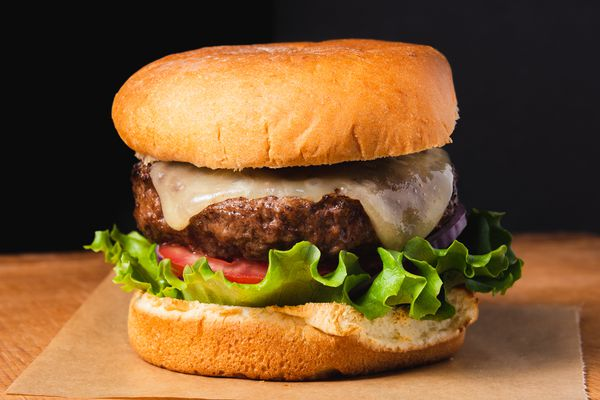 A juicy broiled burger with lettuce, tomato, cheese