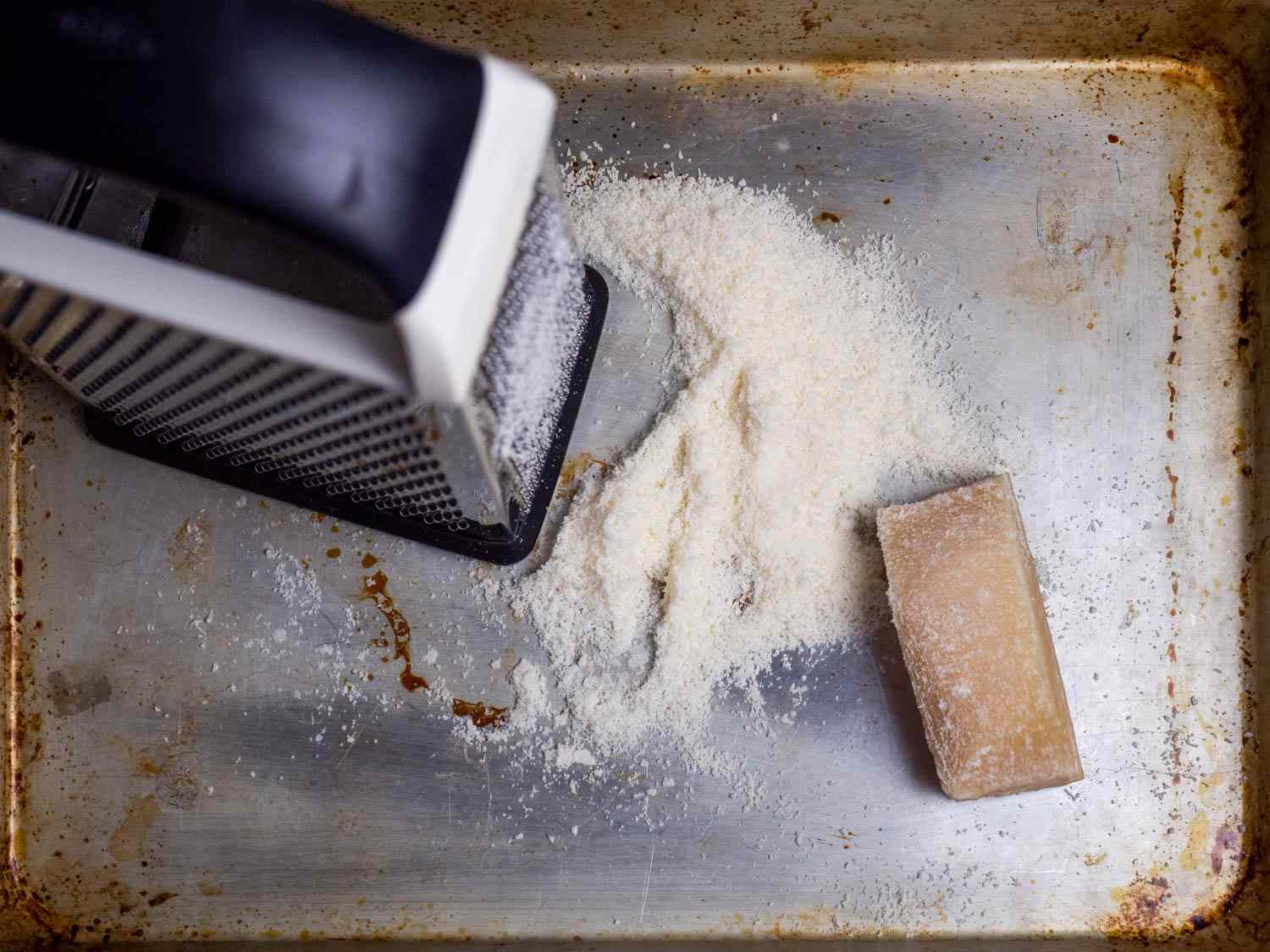 A box grater sites on a rimmed baking sheet alongside a pile of grated cheese and a chunk of Parmesan.
