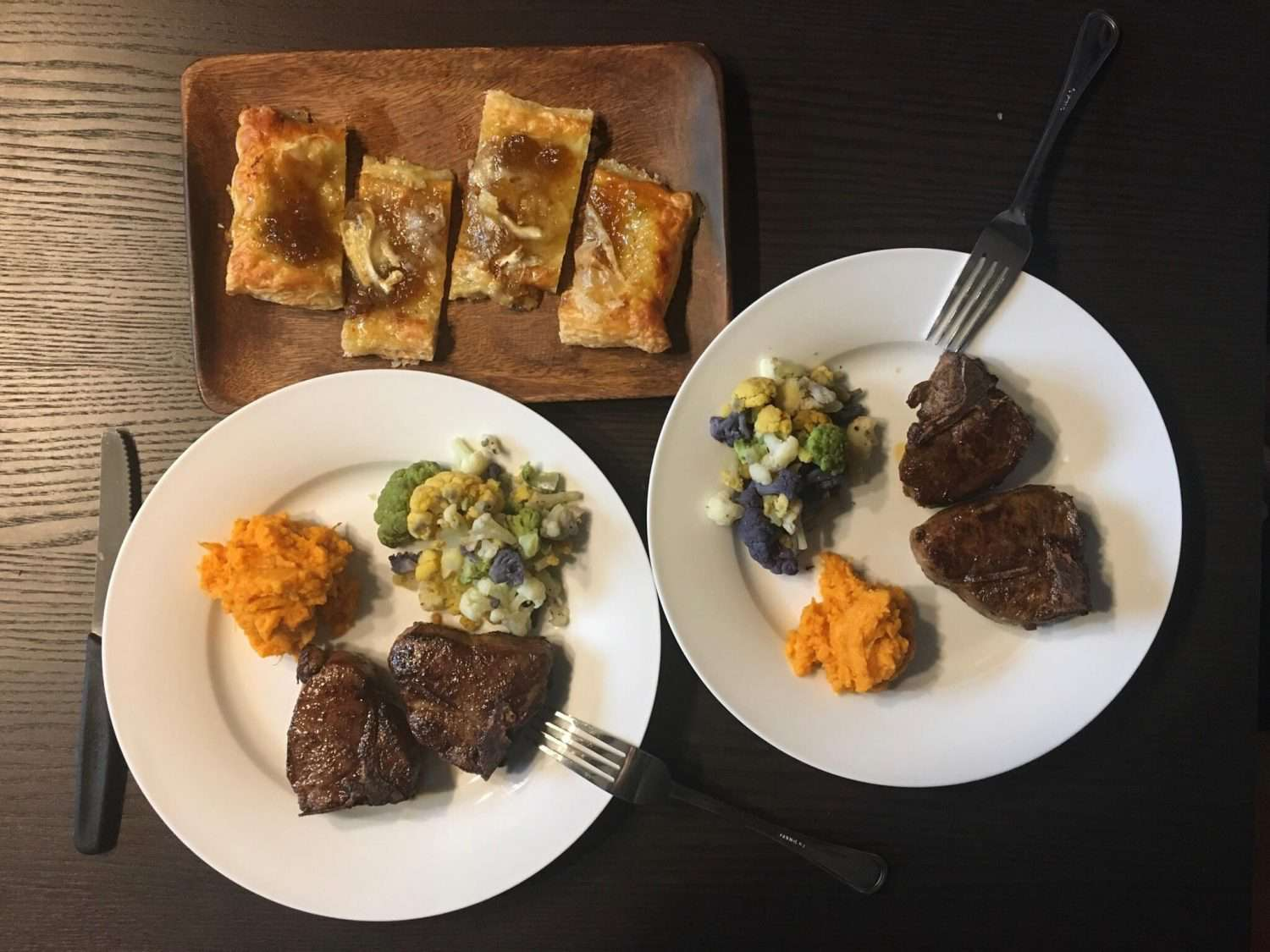 overhead view of an easter dinner, with lamb loin chops, roasted cauliflower, and mashed sweet potatoes