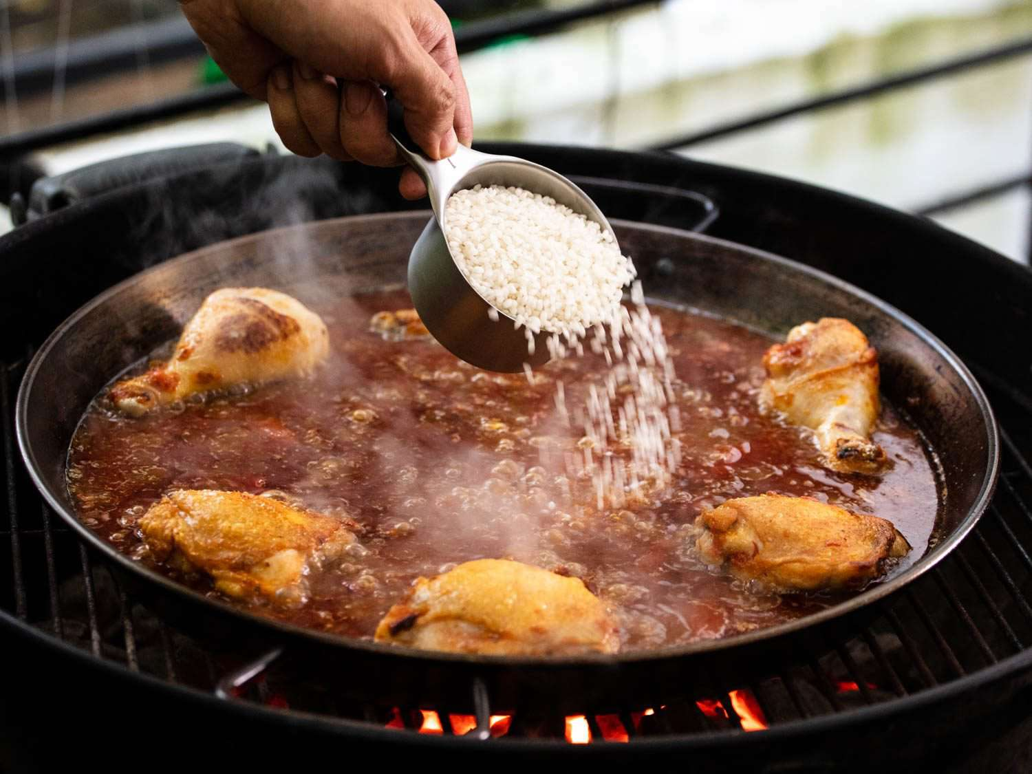 Adding rice to boiling liquid in the paella pan.
