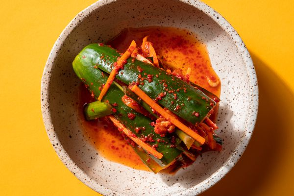 Overhead of a piece of stuffed cucumber kimchi in a small serving bowl.