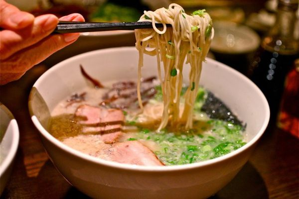 A bowl of ramen. Someone is using chopsticks to lift noodles above the bowl.