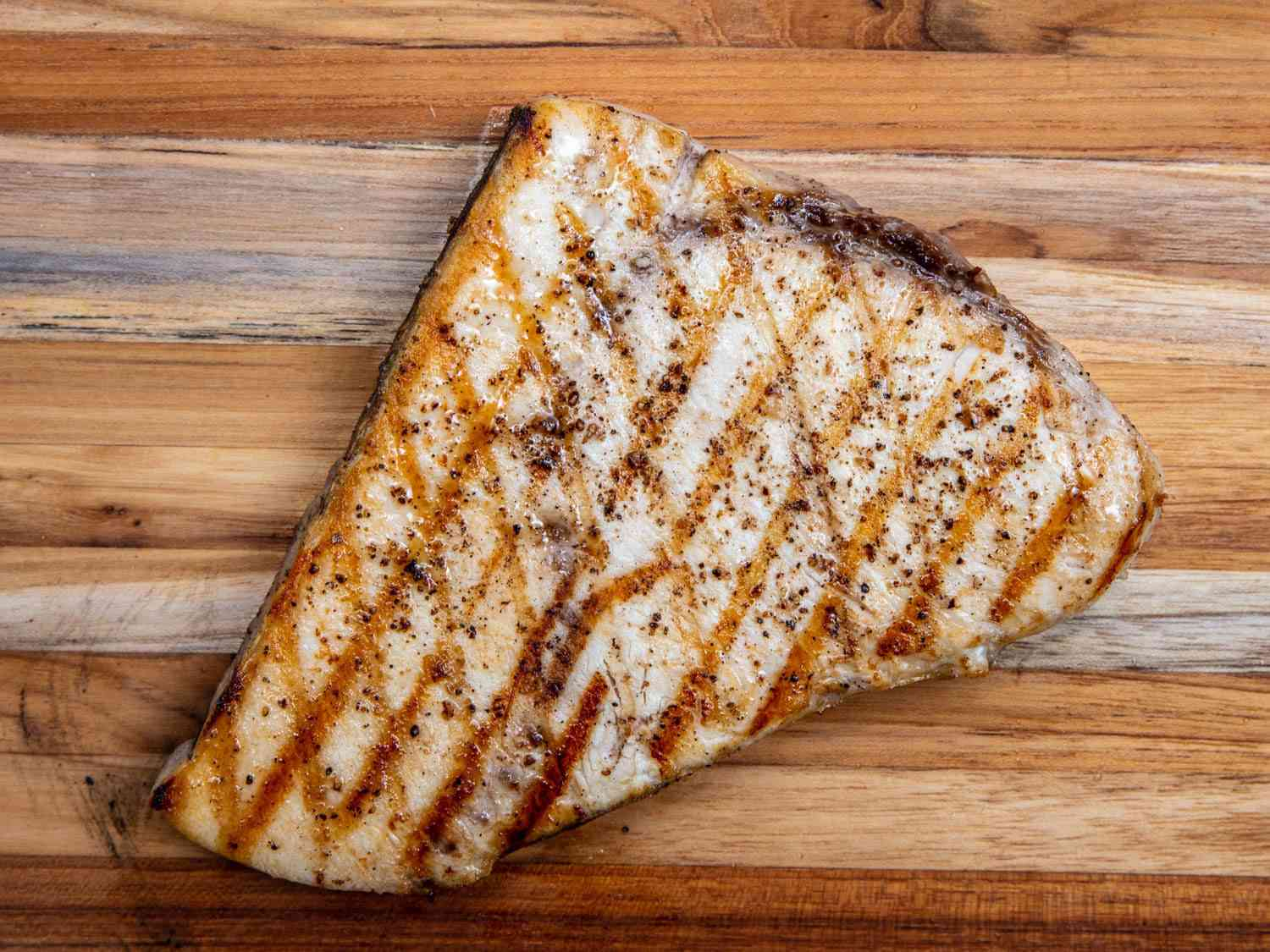 A piece of grilled swordfish steak on a wooden cutting board, ready to be served