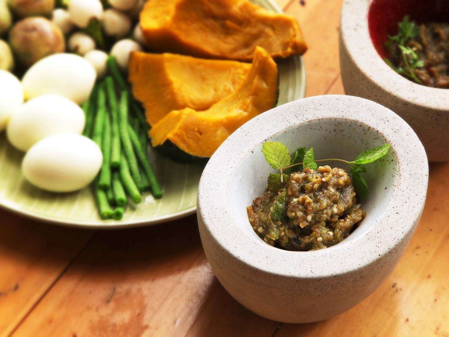 A dish of nam phrig noom (Northern Thai roasted-chili dip) next to assorted items for dipping