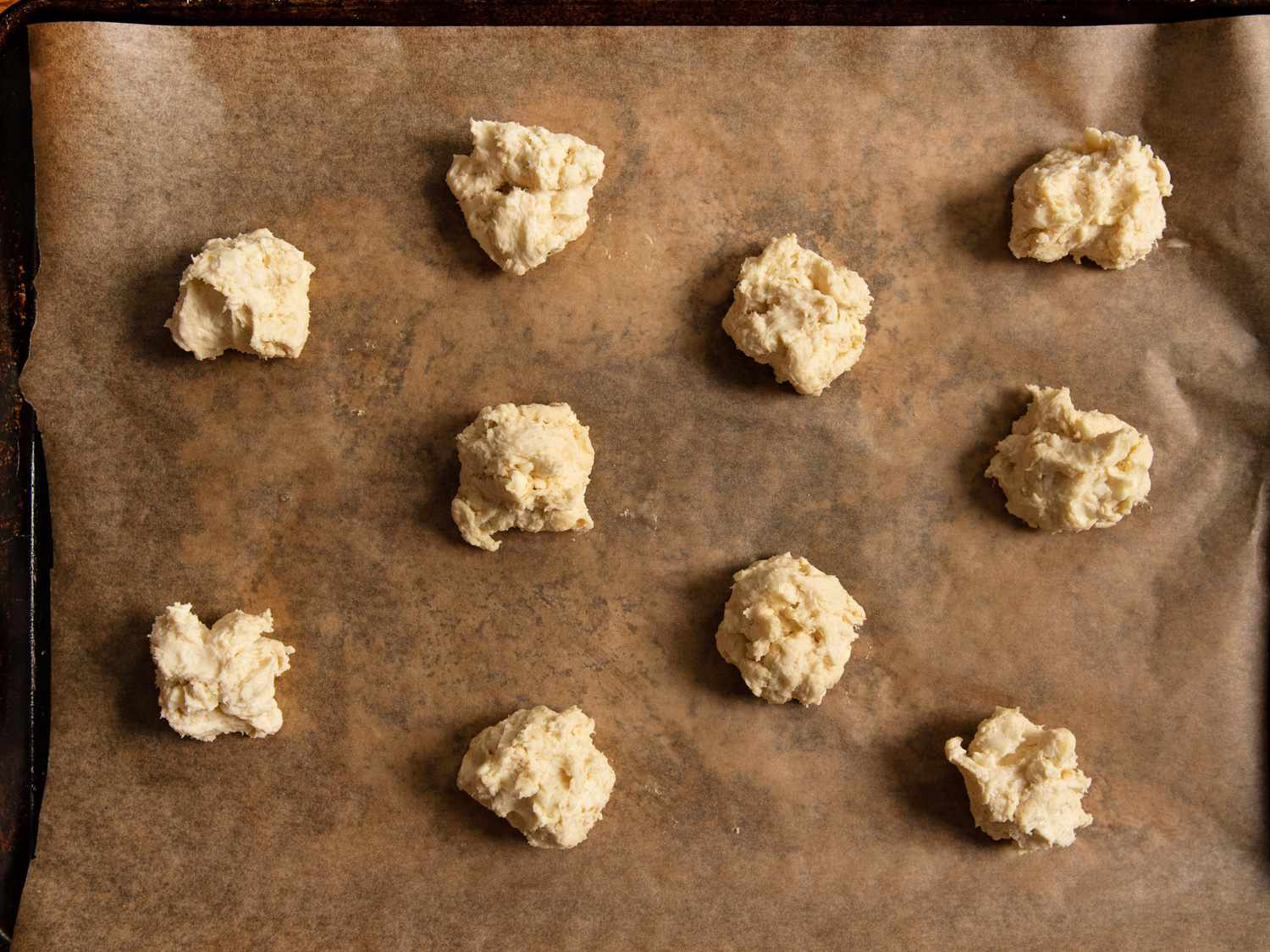 Dollops of biscuit dough on a parchment-lined rimmed baking sheet.