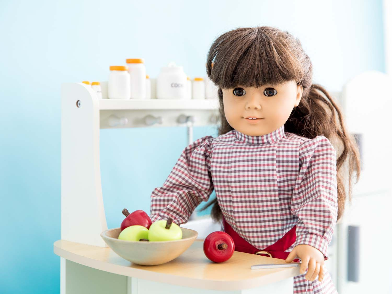 A Samantha doll standing over a bowl of apples at a counter in a white doll kitchen