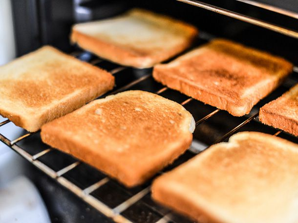 Six slices of toast on an oven rack.