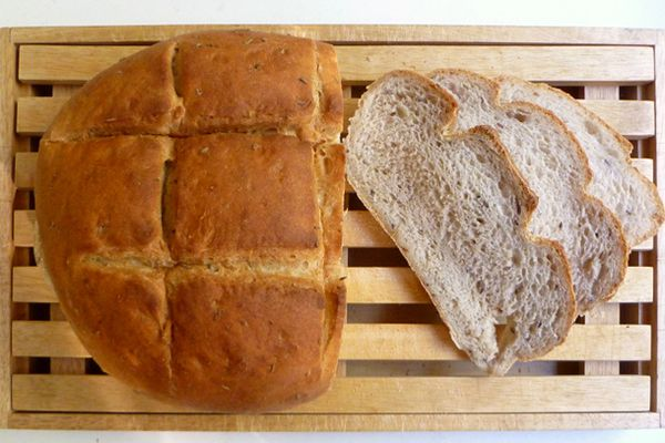 A boule of homemade bread on a wood slat board with three slices next to it.