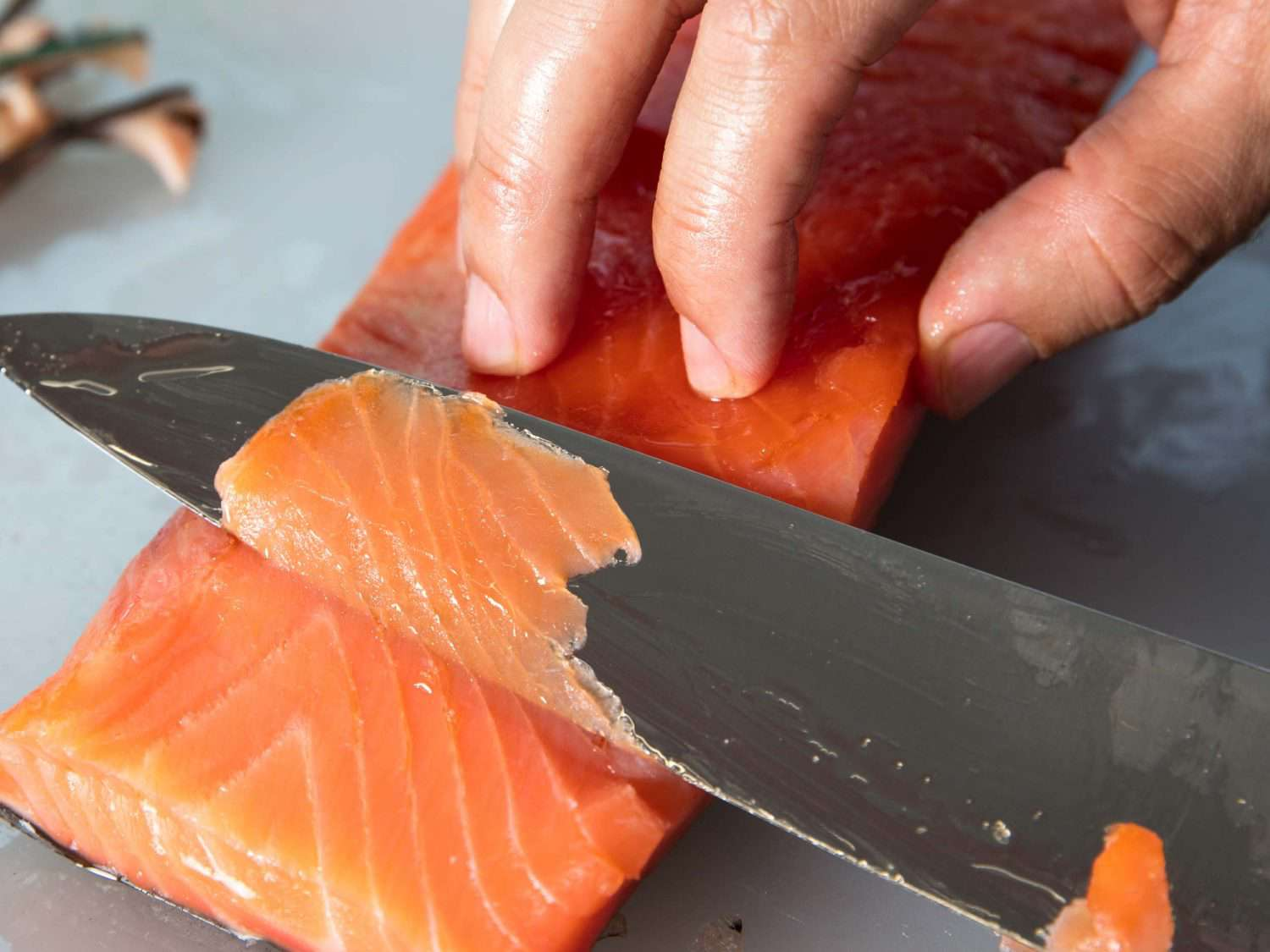 Slicing thin pieces of salmon with the blade of a chef's knife