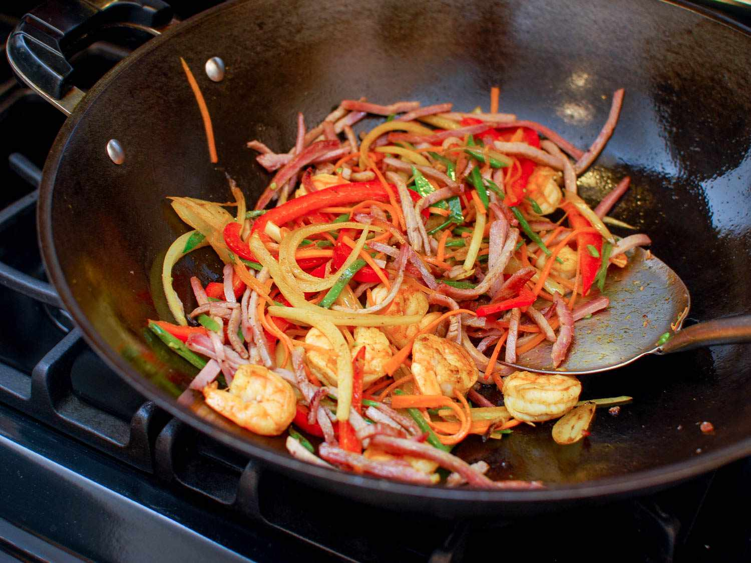 A metal spatula stirring a wok full of shrimp, pork, onion, bell peppers, snow peas, carrots, and curry powder.