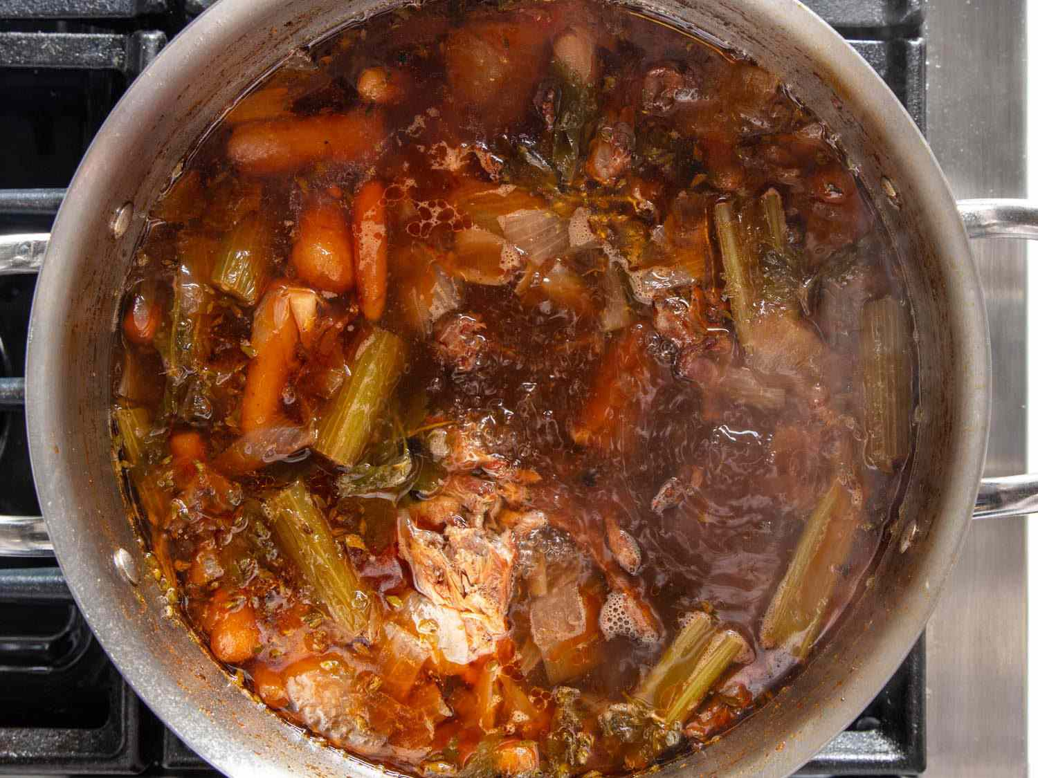 Closeup overhead of duck stock simmering in a stockpot.
