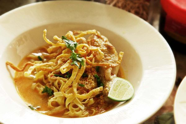 White bowl containing Khao Soi Gai (Northern Thai chicken curry and noodle stew) garnished with herbs and a lime wedge.