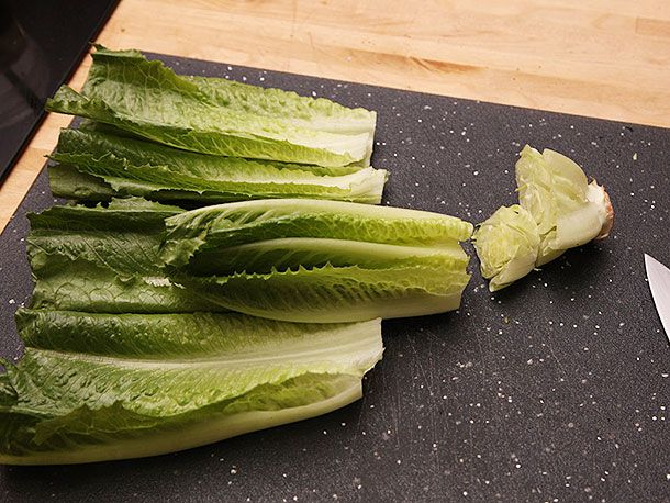Chopping off the end of a head of romaine lettuce and separating it into leaves