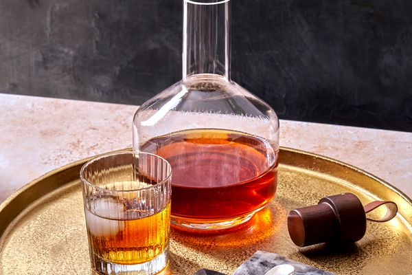 spiced rum in a glass with a decanter filled with the full batch