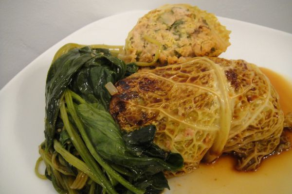 Asian Cabbage Rolls with Spicy Pork on a plate with sauce and greens.