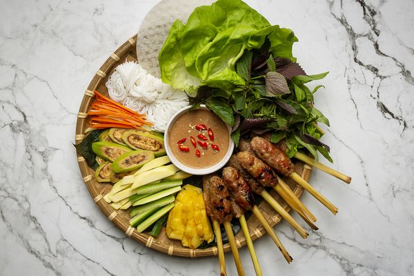 Overhead view of nem lui Hue (grilled lemongrass-skewered pork) on a platter along with vegetables, herbs, lettuces, rice noodles, dipping sauce, and rice paper