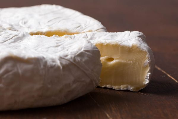 A wheel of brie cheese with a slice cut and slightly pulled away to show the creamy interior.