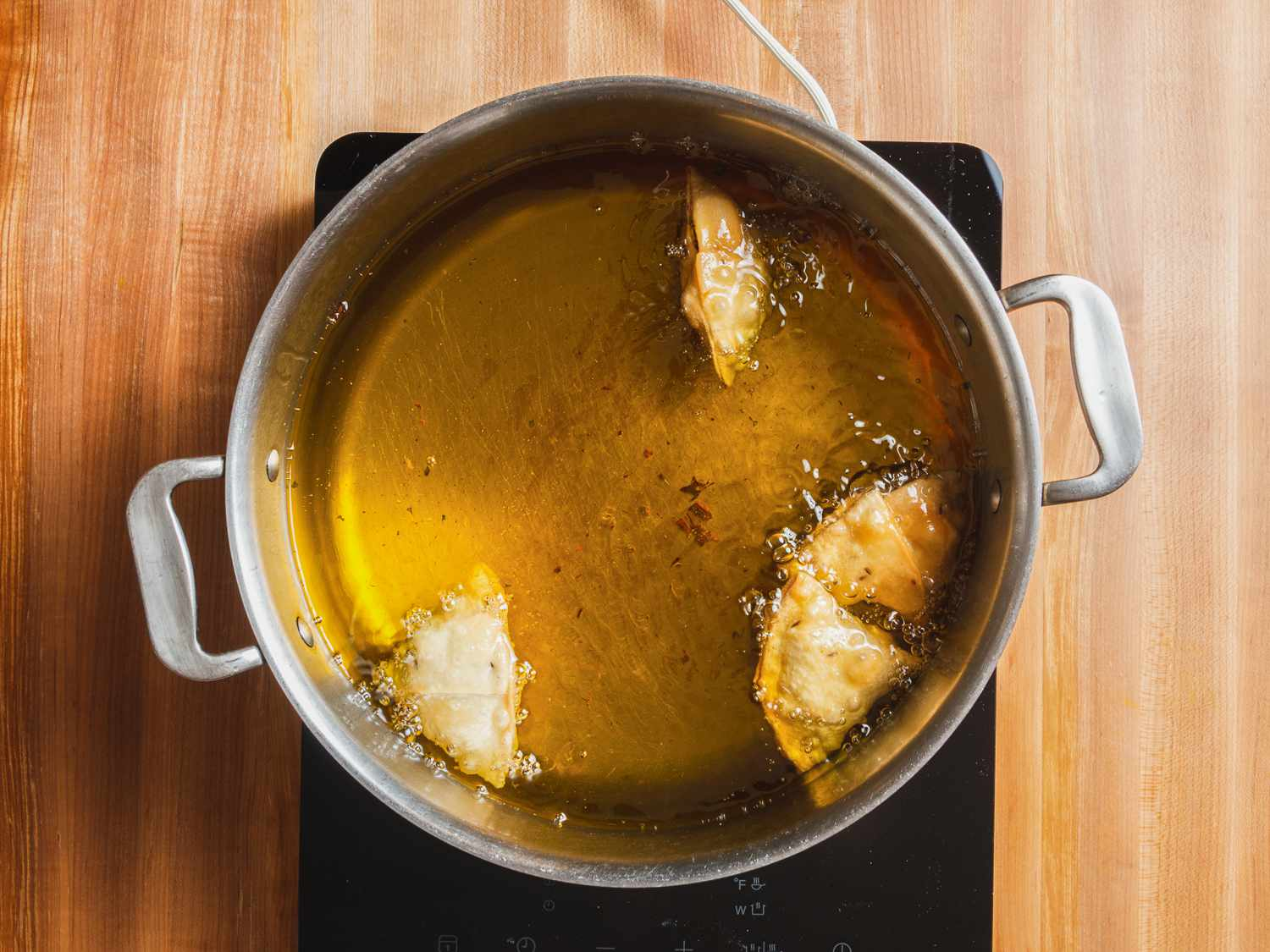 Kheema samosas viewed from overhead, frying in a pot of oil