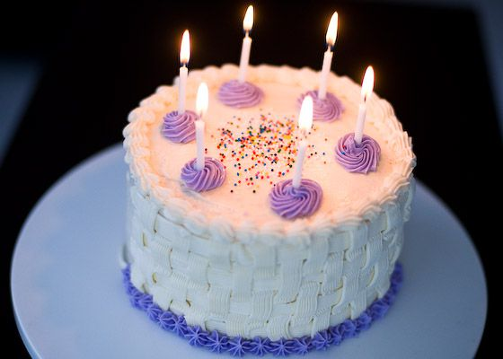 Vanilla birthday with lit candles, sprinkles, and purple decorative frosting