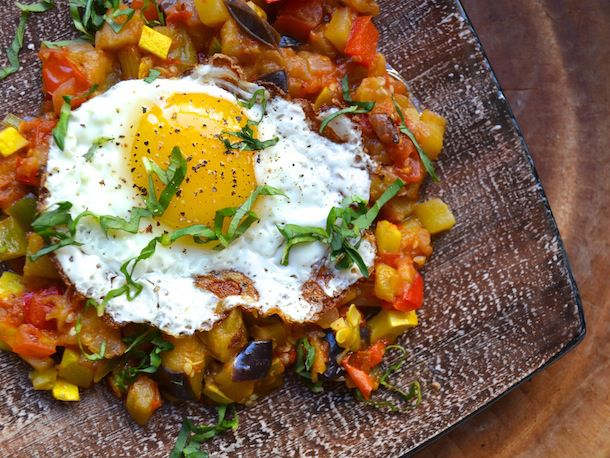 Ratatouille with a fried egg on top, garnished with chopped parsley.