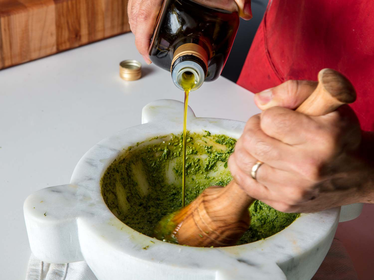 Drizzling olive oil into basil, pine nut, and garlic paste in a marble mortar to make into traditional pesto sauce.