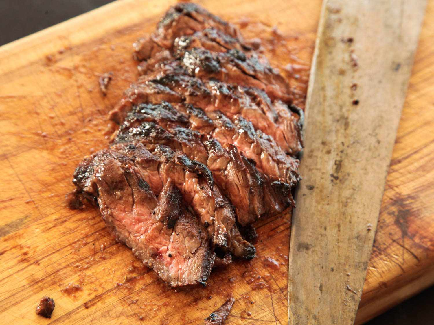 Sliced cooked skirt steak for fajitas slightly fanned out on a wooden cutting board, next to a large knife.
