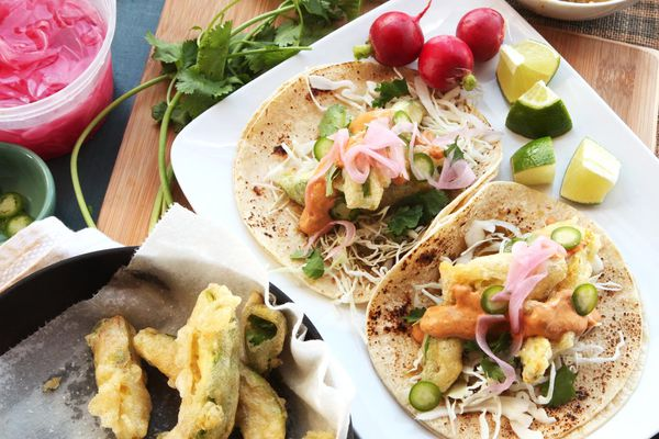 A platter of tacos with radishes, lime wedges and cilantro on the side.