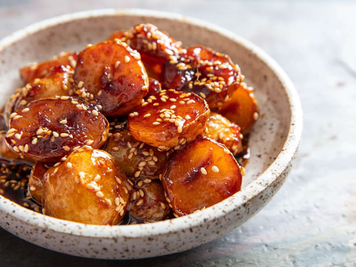 Closeup side view of a bowl with sweet soy-glazed potatoes and sesame seeds