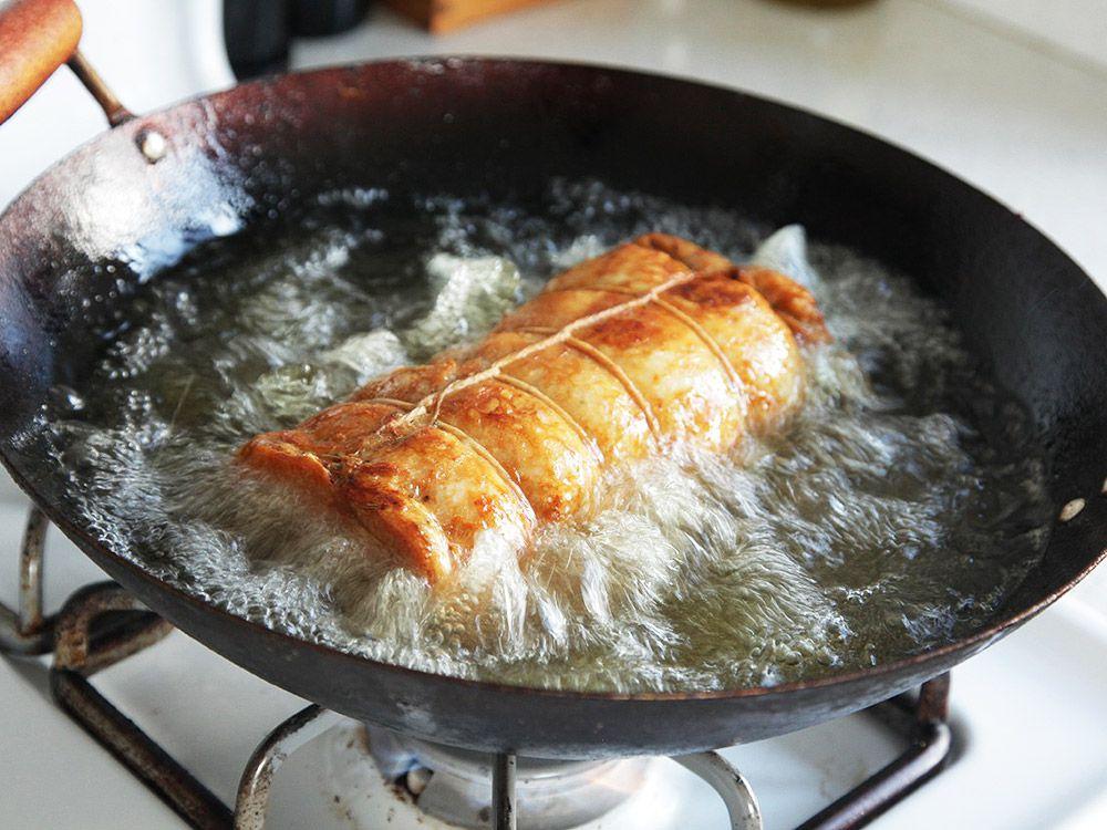 deep-frying turkey porchetta in a wok