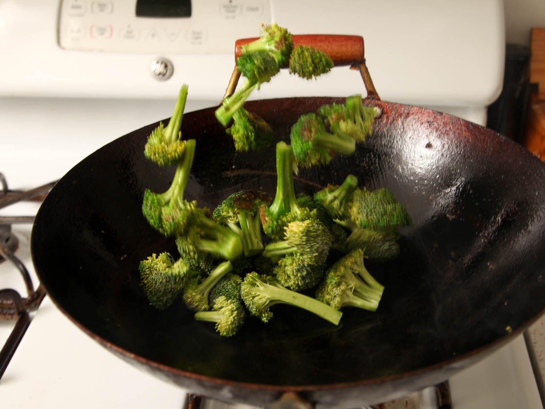 Stir-frying broccoli florets.