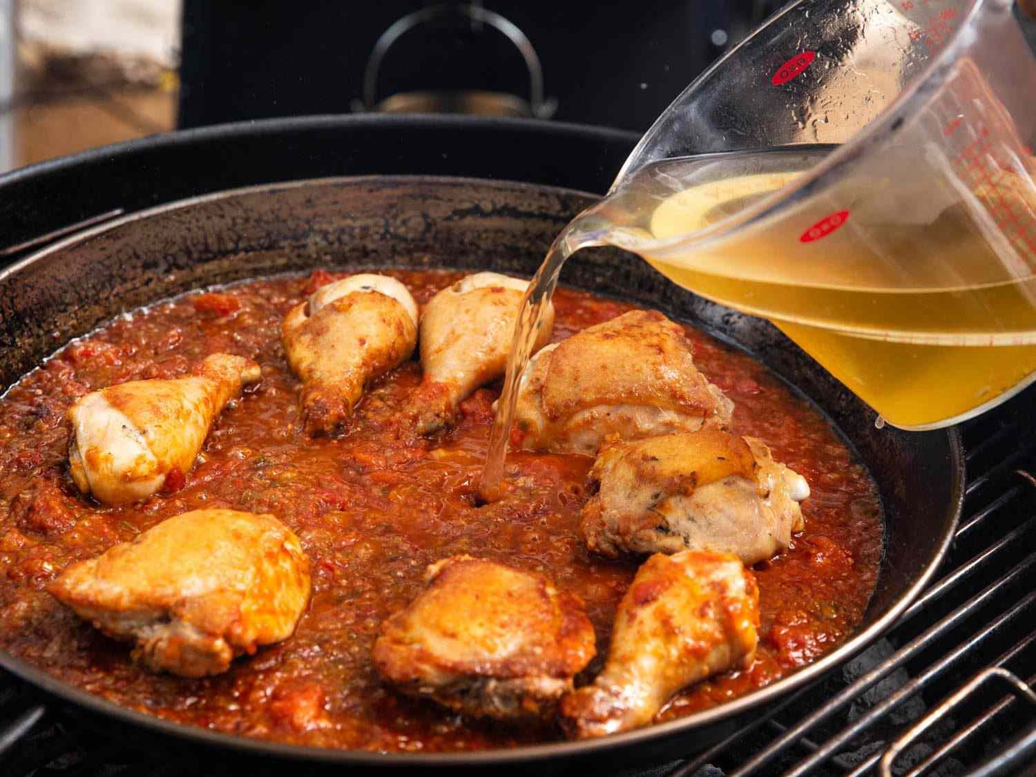 Adding stock to the paella pan after browning the proteins and aromatics.