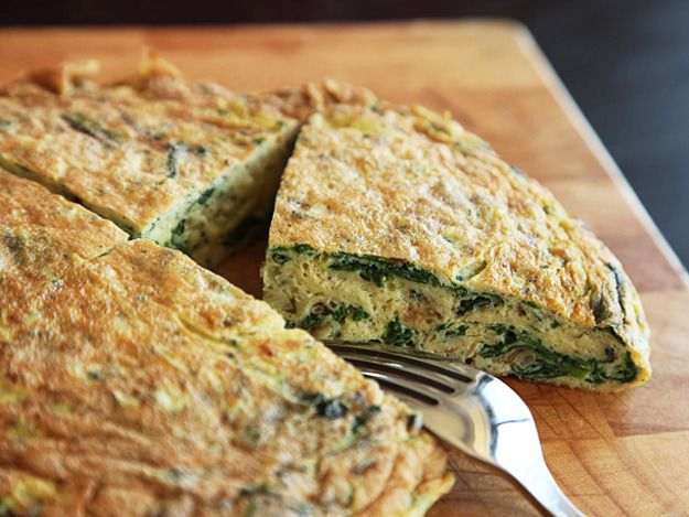 A puffy ramp frittata with a wedge cut out so we can see the inside. There's a fork on the cutting board next to the frittata wedge.