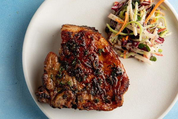 pan seared pork chop with a side salad on a plate