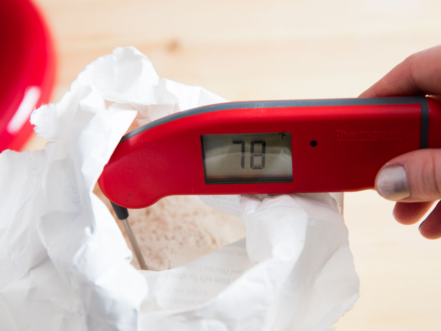 A thermometer in an open bag of flour, registering 78 degrees Fahrenheit