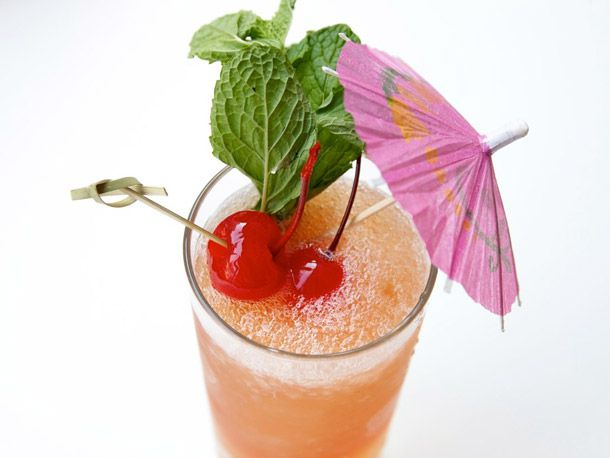 Zombie punch cocktail with cherries, mint, and an umbrella