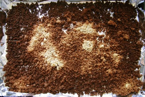 A sheet pan of burned breadcrumbs showing the ways different areas of the pan brown faster than others.