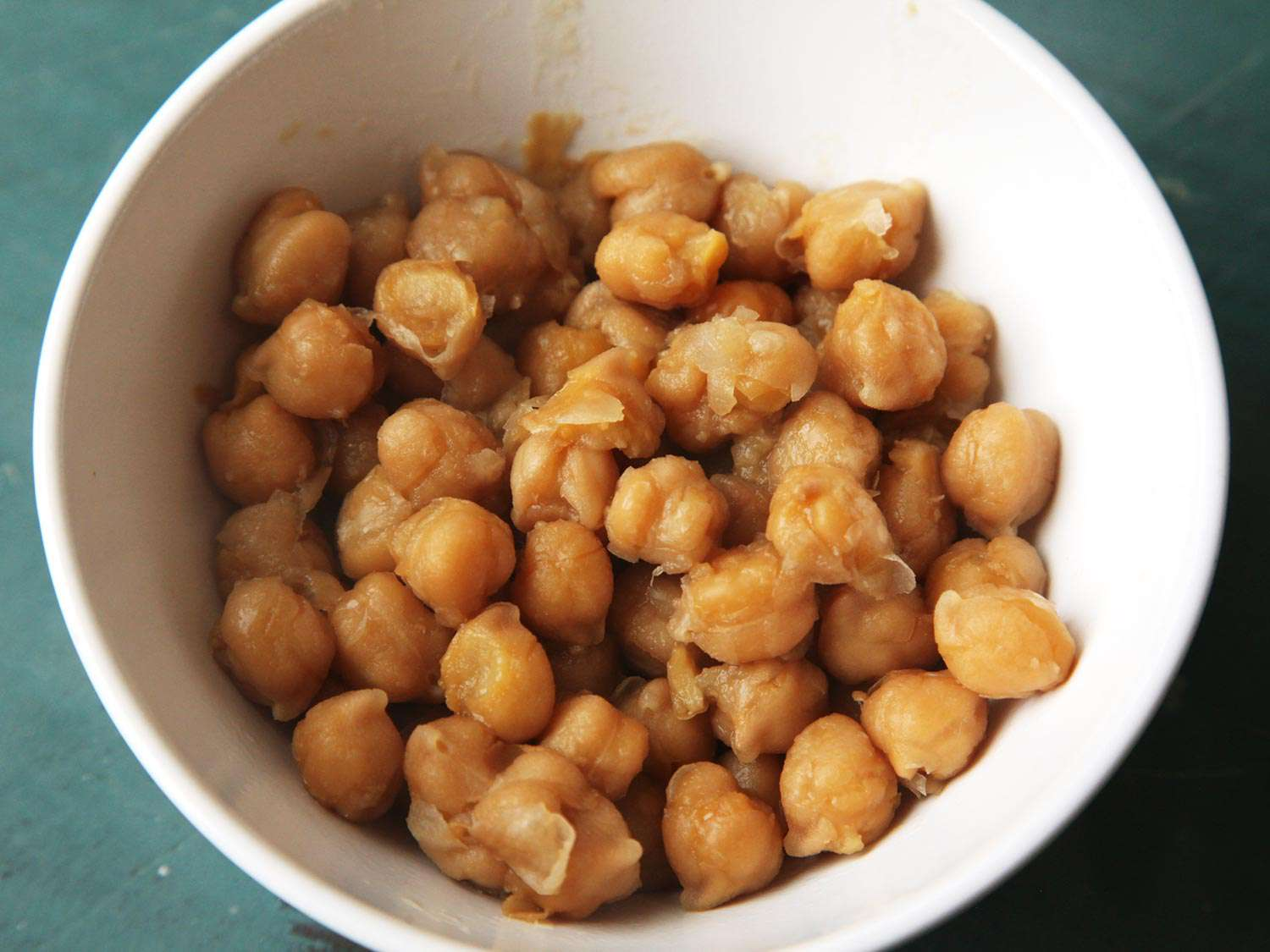 A white bowl of thoroughly cooked, falling-apart chickpeas