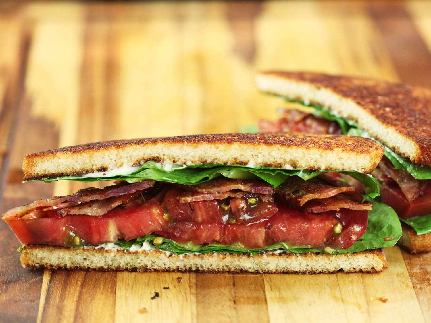 Interior view of a halved BLT, with layers of mayo, lettuce, bacon, and tomato visible between toasted bread slices