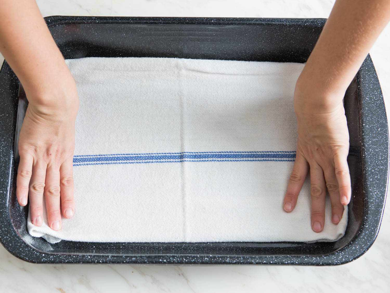 A blue and white cotton towel being placed into the bottom of a roasting pan