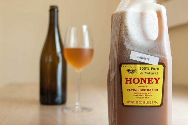 A half gallon bottle of honey in the foreground with a bottle and glass of mead in the background.