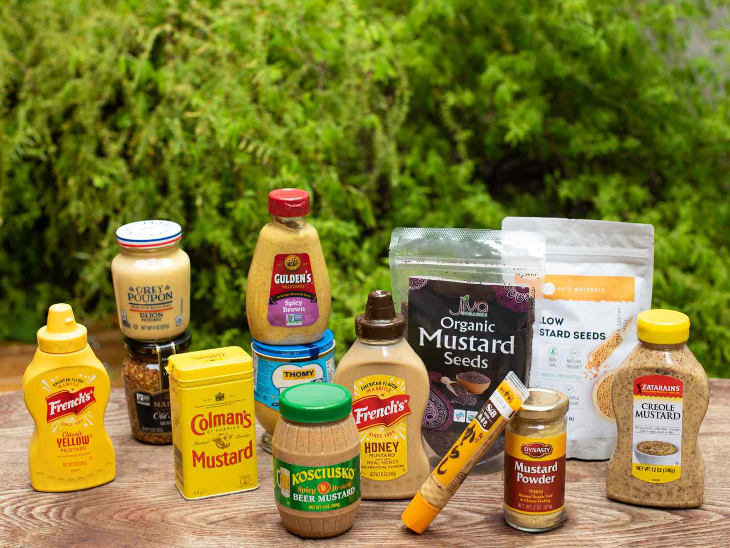 a group of mustard products on a table outside in a backyard