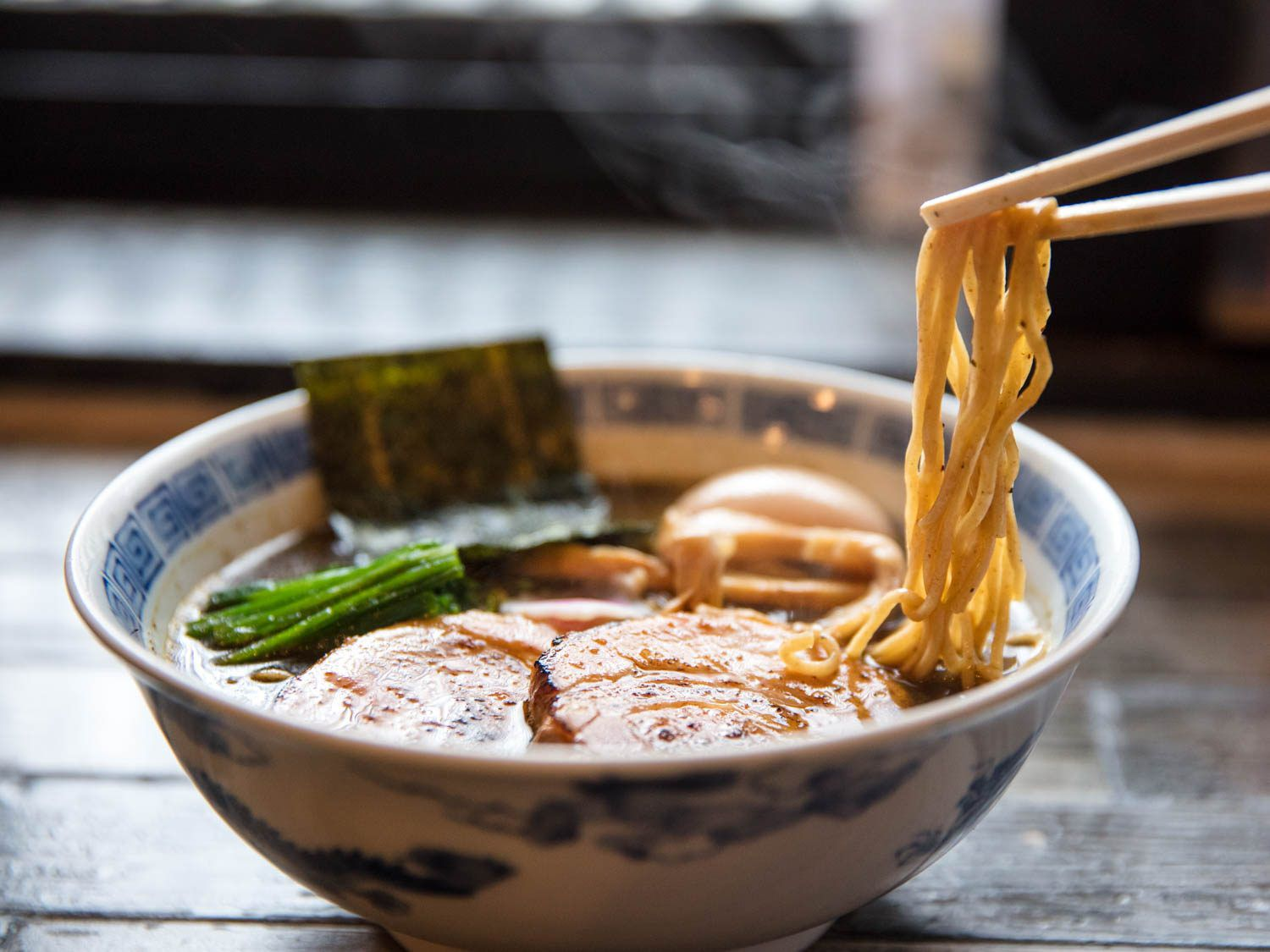 Chopsticks lifting noodles from a bowl of ramen, with nori, green vegetables, pork belly, and egg visible in the background